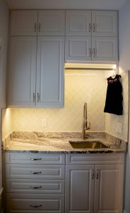 Custom Atlanta laundry room cabinetry with LED under cabinet lighting and glass backsplash