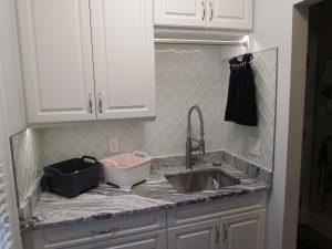 Brookhaven Laundry Room marble countertop with undermount sink and glass backsplash and hanging rod above