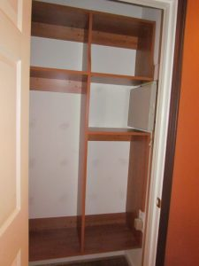 Shelving built and notched around alarm panel and electrical receptacle