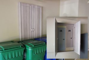 Custom cabinet covers electrical panels in an upscale garage
