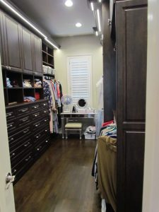 Handsome walk-in closet features an overhead valence with crown molding and LED lighting