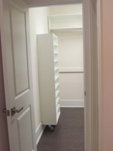 Small shelf unit has wheels and a hinge, pivots out of the way of the pull-down attic stairs