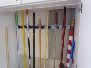 Broom Holders Behind Doors Close-up