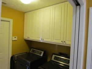 Upper Lexington Cabinets with Satin Nickel Knobs behind Pocket Door