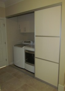Almond Cabinets with Contemporary Satin Nickel Pulls behind Aluminum Sliding Door