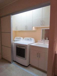 Lighted Laundry Closet with Cabinets behind Aluminum Sliding Door