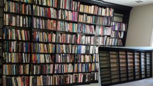 Wall to wall floor to ceiling bookshelves in black melamine packed with books