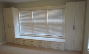 Wide bench seat and tall cabinets surround window