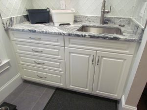 Clean and functional Atlanta laundry room renovation sink cabinet with drawers and marble counter