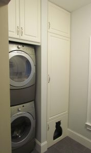 Stacked washer dryer next to tall pantry cabinet with custom cat shaped door to littler box