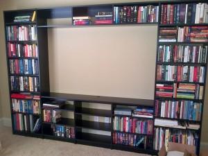 Black melamine bookshelves surround space for a flat screen TV