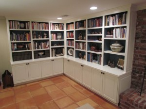 Painted family room built-ins line two walls with base cabinets, counters and upper shelves