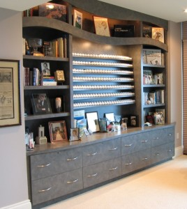 Built in wall unit with curved trim, shelves for a golf ball collection, and wall to wall lateral file drawers