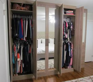 Mirrored wardrobe features hanging spaces, shelves and drawers